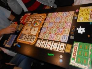 Vue générale des composants du jeu, avec deux plateaux de jeu collectifs et un plateau par joueur.