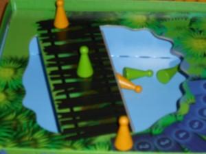 """Quoi ? Des pions tombés à l'eau ? Et bien oui, le """"Ou pas"""" que j'indiquais précédemment révèle la grande subtilité du jeu : on avance de 1 à 4 cases quel que soit le résultat de son dé, même la croix qui figure sur deux faces. Cependant, si l'autre joueur ne vous croit pas et qu'il a raison, votre pion tombe à l'eau, sinon c'est le sien. Simple et très efficace..."""
