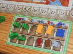 Pour démarrer, chacun dispose d'une brique (valeur 3), de deux céréales (valeur 4), d'une enclume (valeur 5), d'une amphore de vin (valeur 6) et d'un tissu (valeur 7). Attention, les cases d'entrepôt n'ont aucun lien avec la denrée imprimée au-dessus (juste un aide-mémoire)...
