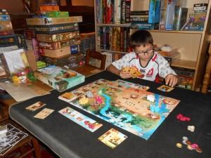 Tristan s'investit tout de suite et plutôt bien dans ce jeu de combos  qu'il semble apprécier très rapidement. Il sait y faire le bougre avec les actions qui se combinent... Ici, il est en train de jouer une carte, avec une autre en-dessous, afin d'en appliquer les effets. A noter que l'on peut activer une carte jusqu'à trois fois à condition, bien sûr, de lui affecter 3 indiens (soit via une ou plusieurs autres cartes, soit via les petits indiens en bois)...