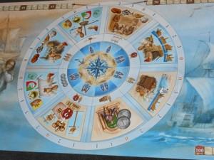 La géniale roue d'actions ! Les 8 secteurs sont amovibles et offrent chacun une action. Comme dans Puerto Rico, son illustre aîné de 11 ans, le premier joueur va choisir une action, bonifiée (symbole juste en-dessous de la tuile) pour lui, et tous les autres joueurs pourront aussi la réaliser (mais sans le bonus). Petit trouvaille kramerienne : la main d'oeuvre en bleu associée à l'action choisie (zone la plus proche du centre), laquelle sera modifiée d'une manche à l'autre puisque les secteurs seront redisposés au hasard... Deuxième trouvaille : le tarif à payer en thalers, inscrit le plus à l'extérieur des secteurs (seulement valable pour les tuiles bleues).