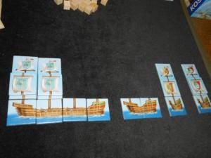 Bon, mes bateaux avancent, mais que c'est dur de satisfaire aux contraintes requises ! En effet, sur un même bateau, seuls des symboles identiques de mâts et de voiles sont autorisés. De plus, lorsqu'un bateau est terminé, on obtient un bonus par mât du bateau achevé. Par exemple, lorsque j'ai terminé mes deux petits bateaux de droite, j'ai obtenu deux fois un bonus. Ceux-ci peuvent être des thalers, des matelots, ... mais surtout des voiles et des mâts à symbole joker (couronne), plaçables n'importe où. J'en serai particulièrement friand...
