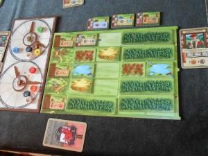 La zone de Laurent en fin de deuxième manche, avec 4 cartes jouées, dont le Seigneur fédoal, lequel lui permet d'avoir un étalage privé de bâtiments à construire...