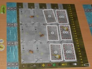 Chaque joueur dispose d'un port, représenté par ce plateau individuel, divisé en une esplanade de 4 x 4 cases (pouvant accueillir des denrées ou des bâtiments), une zone d'arrivée de bateaux (à gauche) avec 3 quais et une zone d'arrivée de camions avec des contrats (en haut) avec 4 espaces...