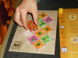 Tristan est en train de prendre un lot de 4 tuiles (une orange sanguine, un citron, un citron vert et un pomelo). Il paiera 4 d'argent pour cela et devra donc les placer toutes sur le plateau, avec les éventuels pions à sa couleur, sous peine de perdre 3PV par tuile non placée...