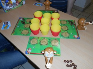 Et voici à quoi ressemble la chose : un groupe de paniers, de deux couleurs, avec des empilements de deux aux quatre angles et au centre, ainsi qu'un singe par côté, espacé des paniers par un petit plateau individuel sur lequel vont se placer les paniers collectés. Collectés ? Oui, car à chaque fois que vous lancez une noix de coco dans un panier, vous gagnez ce panier, celui-ci venant se placer sur votre plateau, d'abord au sol (pour les trois premiers) puis au-dessus. Tout un programme, non ?