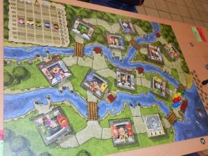 Même si notre nombre de joueurs devrait nous obliger à jouer sur 2 tables seulement (10 joueurs), on opte pour la répartition sur trois tables, avec 3, 3 et 4 joueurs. On tire au hasard l'affectation de chaque joueur et on installe, ensuite, chaque table groupe par groupe, afin que personne d'autre que la tablée ne connaisse notamment le féticheur installé. Voici la table où je me trouve, avec Sylvain (rouge), Quentin (bleu) et Tristan (jaune)...
