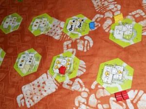 Premier tour de jeu. Fabrice, en tant que premier joueur, a opté pour une enchère d'un keyple bleu près de la tuile qui permettra d'avoir 1 transport + 1 blé + 1 amélioration. J'ai choisi de miser 2 keyples rouges près de la tuile qui donnera soit 1 mouton soit 1 blé soit 1 talent. Ensuite, Tristan a choisi de prendre 2 blés avec un keyple rouge. Enfin, Françoise a placé deux keyples jaunes sur la tuile permettant de prendre 1 mouton. A noter qu'elle décalera ses mises suivantes sur le bord de droite de l'hexagone pour une meilleure lecture des mises...