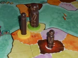 Lors de la mise en place, une tribu noire, de taille 1 et de force 1 est placée au centre de l'Afrique. Ensuite, Tristan a placé une tribu de même couleur et de même force, mais de taille 2, dans une zone adjacente (il respecte la contrainte : maximum une caractéristique différente). Pour qu'on reconnaisse sa tribu, il a placé un anneau jaune dessous. Ensuite, j'ai placé un pion de même taille et même couleur que lui, mais de force 2, dans une zone adjacente. Chacun de nous a reçu les récompenses prévues par la couleur de la zone d'arrivée.
