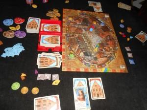 La partie se déroule à 3 joueurs, avec un double-sabot pour placer les cartes (récupéré dans un sempiternel Mille Bornes trouvé en vide-grenier). En effet, les cartes ayant tendance à glisser les unes sur les autres, et comme il ne faut pas connaître la couleur du dos de la carte qui suit, cet investissement, lourd ;-) a dû être fait pour jouer correctement... A ce stade de la partie, Maitena a su profiter de nos couleurs de cartes initiales, incompatibles avec nos débuts de canaux, pour prendre seule la tête sur cet axe et tourner son marqueur de majorité sur sa face 4PV.