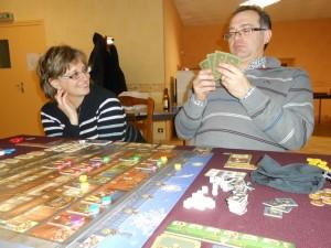 Ce jeu, aussi sérieux soit-il, nous permet aussi de passer de bons moments de rigolade, lorsque l'un ou l'autre couine ou passe un temps négligeable à choisir sa main de cartes. Ici, Béatrice fait -gentiment- remarquer à Fabrice que, peut-être, il devrait choisir plus vite... Mais c'est clair que ce moment de choix peut s'avérer très délicat, surtout quand on mesure que les cartes que l'on ne prend pas seront forcément jouées le tour suivant...