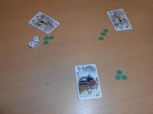 """Le principe est ultra-basique : à chacun des 12 tours, le premier joueur choisit le nombre de dés qui seront lancés (1, 2 ou 3) puis chaque joueur choisit une de ses 13 cartes (valeur 1 à 13) parmi celles qui lui restent en main, accompagnée d'un jeton. Ensuite, le ou les dés sont lancés par le premier joueur. Celui-ci décide ensuite si on révèle les cartes tout de suite, ce qui permettra au joueur ayant joué la carte la plus haute, mais en-dessous du résultat des dés, de récupérer les jetons. S'il préfère, il peut dire """"double"""" et ajouter un jeton, ce qui contraint les autres à faire de même ou à abandonner. S'il est seul en course, il remporte les jetons misés, quelle que soit la valeur de sa carte... Ci-dessus, un exemple de résolution qui me permet d'empocher les 9 jetons grâce à ma carte 9, la plus haute en -dessous du 10 lancé."""