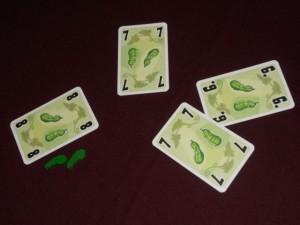 Voici le dernier pli de notre première manche, fatal à Tristan puisqu'il empoche 2 cornichons, se retrouvant contraint de prendre avec son 8 (et il y a 2 cornichons dessus). Mais la partie n'est pas finie... En effet, jusqu'à 5, tout va bien. Par contre, dès que vous avez 6 cornichons vous êtes éliminés ! Et la partie se poursuit avec les autres joueurs jusqu'à ce qu'il n'en reste plus qu'un...