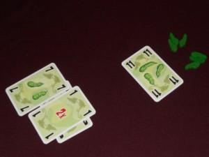 Voici la fin de manche déjà mémorable où Fabrice se fait éliminer, lui qui n'avait aucun cornichon juste avant ! En effet, avec son 11 il empoche 6 cornichons, Tristan ayant brillamment réussi à emmener son 1 au bout pour doubler la prise de celui qui fait le pli !!! Et ce n'est pas facile... Pourquoi ? Tout simplement parce que la règle est bien retors : à son tour, on doit soit jouer une carte de valeur au moins égale à la plus forte jouée, soit jouer sa plus basse !!! Tout le sel du jeu vient de là, vous en conviendrez...