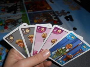 Ma main de cartes pour la 5ème manche, avec un gros axe pistes grise et rose, sans négliger la bleue du roi. Dans les faits, je laisserai tomber l'une des deux roses, mes partenaires n'en jouant pas assez pour m'obliger à jouer la seconde pour avoir le bonus de 3 cases...