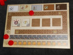 Chaque joueur dispose d'un mini-plateau de positionnement et voici le mien en fin de première manche. On peut voir que j'ai collecté une ressource de tabac, que j'ai avancé pas mal sur la piste marron (d'où les deux tuiles de développement empochées : je renforce les pirates de 2 points contre tous les autres joueurs et j'aurai 7PV en fin de partie), que je suis toujours à 0 sur les canons et que je n'ai pas bougé au niveau de l'or (toujours la pièce de départ, autre système très feldien : on peut les dépenser pour se rajouter des points d'action, un peu dans l'esprit des ouvriers dans Die Burgen von Burgund)...