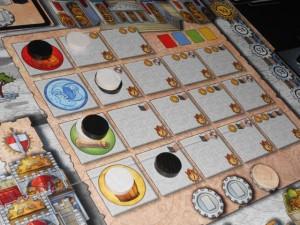 L'une des zones du plateau sur laquelle chaque joueur doit choisir deux progressions avant de démarrer : Tristan, en blanc, décide de prendre un magister rouge (percepteur) et un bleu (religieux), alors que j'opte, en noir, pour un bleu (religieux) et un jaune (marchand). Nous empochons donc deux cartes chacun, lesquelles rejoignent notre main de 8 cartes de courtiers pour arriver à 10. Ensuite, pour attaquer la première manche sur 9, nous séparons nos 10 cartes en deux tas de 5 et, hop, c'est parti !