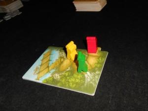 """Chacun joue jusqu'à 5 cartes face cachée, de même type (bronze, argent ou or), et elles sont révélées simultanément. Le premier sur le parcours avance d'autant de cases qu'indiquées sur ses cartes, puis le deuxième, etc... Si on termine un déplacement sur un autre pion, on avance sur la prochaine case libre. Si on """"sort"""" de la tuile, on en ajoute une autre. Puis on repioche des cartes : 2 si on a joué des cartes bronze, 1 pour de l'argent et 0 pour de l'or. Et c'est tout..."""