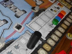 Petite explication du déroulement du début d'une manche. D'abord, chaque joueur choisit un jeton bonus carré parmi les 7 proposés (sorte d'action supplémentaire qu'il pourra exécuter pendant la manche). Selon la case d'où il l'a pris, il se retrouve plus ou moins loin dans l'ordre du tour qui est alors réajusté. Ensuite, le gros marqueur de phase (cylindre noir) est avancé sur la première des deux cases d'action. Chaque joueur pourra donc en réaliser une parmi les 5 : acheter une mine, acheter une machine à vapeur, placer une cité, placer un ingénieur, placer et/ou déplacer des gueules noires. Bien sûr, je vous épargne les contraintes requises à chaque fois...