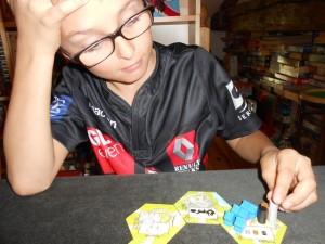 Tristan se prend un peu la tête :-) et il empile ses nombreux cylindres obtenus sur cette tuile de production où il a joué pas moins de 1 +2 + 3 meeples bleus !