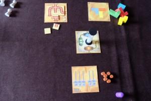Le premier joueur choisit un type de puzzle et prend la première carte de la pile ainsi que le matériel associé, puis le deuxième fait de même, puis le troisième. Enfin, simultanément, chacun essaie de réaliser son puzzle. Le premier qui termine retourne le sablier, ce qui laisse une minute 30 de plus aux autres pour y parvenir. Ici, seul Tristan a réussi son puzzle de tuyaux, alors que Maitena a raté celui des blocs et moi celui des pesées ! Pas facile...