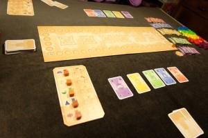 Devant chaque joueur on trouve un étalage de 5 cartes (une de chaque couleur au départ) et on en a 2 piochées au hasard dans sa main. Notre petit plateau individuel, qui tient compte des couleurs d'étages où l'on a placé une tuile, a tous ses marqueurs à gauche. Entre les joueurs, un plateau commun accueillera les 6 pagodes sur les emplacements centraux. On y trouve aussi la piste de scores...