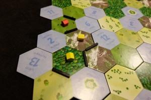 A deux joueurs, deux lacs sont retirés du jeu : le 1 et le 7, du coup on démarre par le lac n°2. Comme trois emplacements l'entourent, Tristan installe un village, puis moi un et Tristan un deuxième. A chaque fois, on entoure l'hexagone de frontières noires (le bord du plateau et les lacs jouant le rôle de frontière). Puis, la nouvelle région ainsi formée, d'une case donc, peut être fusionnée avec une autre adjacente à la condition que le type de terrain ne s'y trouve pas déjà. Facile. Puis, on peut fusionner deux régions, dont l'une au moins est adjacente à celle nouvellement formée, à la double condition d'y avoir au moins un village à soi ET que chacune de ces deux régions aient au moins un type de terrain non présent chez l'autre. Relisez cette phrase. Tout s'y trouve ;-)