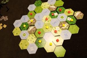 Voici à quoi ressemble le plateau au moment du premier décompte. Les petits marqueurs carrés sont des temples qui viennent renforcer nos positions. Alors, ce décompte, comment se déroule-t-il ? Et bien c'est chaud... D'abord, sachez qu'on décompte uniquement les régions qui se trouvent autour du lac n°5 (donc trois différentes ici). En tout premier lieu, il faut compter le nombre de cases de la région décomptée (pour notre grande ci-dessus, elle est de taille 6). Ensuite, il n'y a pas un mais trois décomptes... Le premier rapporte des points par type de terrain : pour chaque type, celui qui a le plus de villages marque autant de points que la taille de la région. Le deuxième décompte rapporte des points pour celui qui a le plus de villages dans la région : autant de points que de lacs adjacents à la région. Le troisième nous rapporte 1 PV par arme non dépensée. Pas simple du tout...