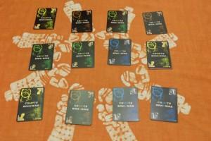 Sur la table principale, chaque joueur dispose ses 3 comptes principaux sous lesquels il placera ses billets de banque, récupérés sur la table secondaire. Fabrice joue les cartes marron, Jean-Luc les bleues, Tristan les jaunes et moi-même les vertes. Au départ, chacun a deux billets, déjà placés sous les comptes de son choix...