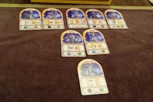 Huit tuiles de personnages sont aussi proposées aux joueurs, lesquels vont pouvoir les utiliser à leur profit. Ce qui est assez déroutant, c'est que ces tuiles ne sont qu'en nombre limité et qu'on peut très bien les avoir toutes vendues en fin de première manche (sur les 4 que comporte la partie) ! Ce qui est sympa, c'est la manière de s'en servir : on les achète en payant le nombre requis de pierres de mana (en rouge en haut) mais il faudra les activer avant la fin de la partie en payant le coût en ressources en bas, sous peine qu'ils ne rapportent rien...