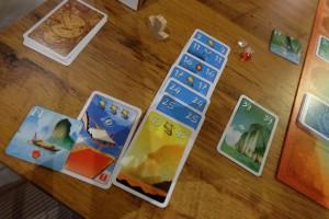 Je m'adjuge une tuile d'expédition de valeur 11, résultant de la position de mon bateau (case 14) et une carte de compétence (3 cerfs-volants dans ma série de cartes jouées) qui me permettra de prendre, plus tard, une tuile de valeur +6 par rapport à ce que je devrais pouvoir prendre...