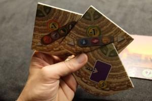 Après un draft en deux tours, ben oui on est dans 7 Wonders quand même, voici les 3 tuiles que j'ai en main : les matières premières coûteront 1 or de plus, les produits manufacturés 1 de moins et la pose de cartes violettes à l'âge 3 seront récompensées de 5 ors. A noter que la pose d'une de ces tuiles prend le tour d'un joueur mais qu'en fin de partie, il empoche 2 PV pour une tuile posée, 5 PV pour deux et 10 PV pour les trois...