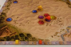 Petite vue générale, alors que l'éléphant jaune de Tristan est présent dans une caravane de 2 tentes (ce qui lui permet de prendre 1 carte jaune et 1 bleue par tour), alors que mon éléphant orange est présent dans une caravane avec 5 tentes de 4 couleurs différentes (donc j'empoche 1 carte de chaque couleur en début de tour). C'est là que le bât commence à blesser : avec 4 cartes empochées par tour, je me dis que, à partir de maintenant, je ne vais plus que placer des tentes isolées histoire de scorer systématiquement 3PV par tour. Ca devient moins excitant...