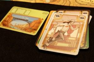A gauche, la carte de la première manche sur 5). A droite, la pile de cartes jouées par nous trois. On va à présent retourner cette pile et appliquer les effets les uns après les autres, dans l'ordre...