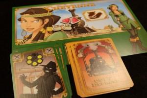 Petite vue de mon plateau avant que nous attaquions la troisième manche : j'ai amassé deux bijoux (valeur de 500$ chacun) et deux bourses (valeur de 250$ à 500$ chacune). En bas, on peut voir que l'une de mes cartes balles a été gentiment donnée à un autre joueur (ce qui lui rajoute une carte sans effet dans son deck et va peut-être contribuer à le contraindre à repiocher 3 cartes à son tour au lieu de programmer une carte)...