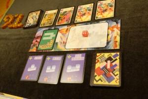 Au centre de la table, on place un plateau principal représentant le musée à réaliser à partir de la carte verte de gauche. En-dessous, on trouve les 3 cartes d'oeuvres à réaliser et, au-dessus, on place 4 cartes d'artistes susceptibles de nous aider dans la réalisation des oeuvres grâce à des pouvoirs spéciaux. Le tout se joue avec des dés : oui, il y aura du hasard... :-)