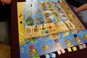 Voici la situation une fois que j'ai remporté la première enchère de cette partie : avec le dé gris, j'ai placé un pirate dans une maison de la péninsule grise, avec le dé vert j'ai fait de même dans la péninsule verte et avec le dé orange j'ai marqué 1PV. Les trois autres joueurs ont profité, eux, d'actions liées aux bateaux sans dépenser d'argent (très utile)...