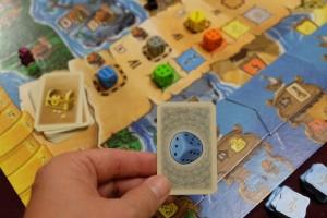 Je commence à comprendre un peu mieux le jeu : en utilisant cette carte perroquet pour changer la face du dé bleu, je le place sur la valeur 6 afin de le mettre le plus à gauche sur la piste d'enchère, tout en ayant décalé le gris sur la deuxième case. Ainsi, je peux espérer, si je emporte l'enchère, placer un pirate dans la péninsule bleue et un dans la grise (deux de mes objectifs)...