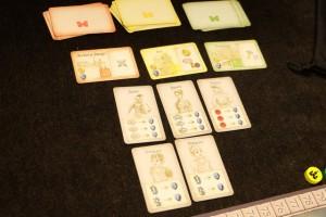 A côté du plateau collectif, on dispose trois piles de bâtiments à venir (rouges : militaires ; jaunes : monétaires ; verts : PV) et trois cartes au-devant disponibles pour le premier tour. En-dessous, on a placé les 5 cartes de personnages prévus pour les parties à deux joueurs (utiles en fin de 3ème, 6ème et 9ème tours : décomptes intermédiaires).