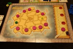 Le plateau collectif accueille une carte du territoire que l'on va tenter de conquérir. Les jetons violets bloquent certaines régions (à deux joueurs). A droite, la piste des manches (avec les sceaux rouges pour indiquer les décomptes intermédiaires).