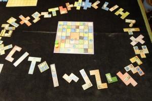 Le jeu est très typé avec son look de tissus patchwork (forcément hein !) et s'avérera très original : on place toutes les pièces de tissu autour de la piste du temps, dans un ordre aléatoire, avec un pion blanc qui sillonnera ce parcours à raison d'une à trois pièces à chaque fois. On devine déjà la règle : on prendra alors la pièce, on s'acquittera de son coût et on la placera sur son plateau individuel en essayant de le paver au mieux...