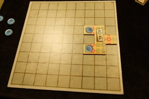 La première pièce que j'ai posée est de taille 6, m'a coûté 3 boutons pour être prise et 6 temps (sur la piste du temps centrale). Elle me permettra d'empocher 2 boutons à chaque fois que mon marqueur de temps dépassera le symbole bouton sur la piste...