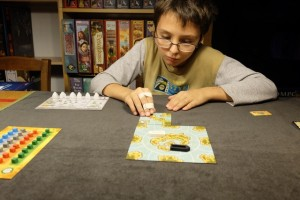 Akrotiri est un jeu à deux, que je découvre forcément avec mon fils. Au départ, une immense tuile est placée au centre de la table, avec des portions d'îles reliées par des liaisons maritimes. Puis, chacun ajoute une tuile connectée et y place des cubes de ressources en fonction de ce qui est indiqué + 1 de son choix. Au cente, on voit nos barges respectives qui sillonneront les mers à la recherche de temples enfouis et qui seront également bien pratiques pour ramasser des cubes de ressources pour les revendre sur l'île centrale...
