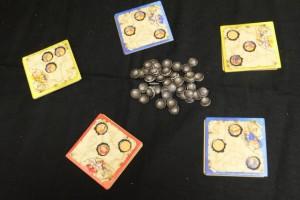 En effet, chacun de nous disposer de trois supports troués visant à être placés sur l'une des 5 cartes objectifs du centre (une par joueur). Le truc, c'est qu'il faut choisir quel support est le plus adapté (les trous ne sont pas au même endroit) et qu'il faut faire apparaître les symboles qui nous intéressent. Le tout, sans oublier que support touché est support joué et que carte touchée est carte choisie... Donc jouer vite ou pas, c'est à chacun de voir...