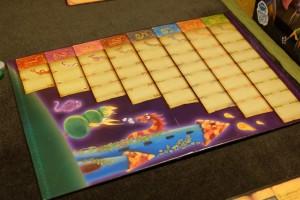 Une partie se joue en autant de manches que nécessaire pour qu'un des joueurs ait atteint la case 8 de la piste de score verticale. Sur ce plateau, on va y placer, progressivement, les tuiles de sort lancées par les joueurs. Vous aurez noté qu'il n'y en pas le même nombre de chaque couleur (une de 1, deux de 2, etc...)