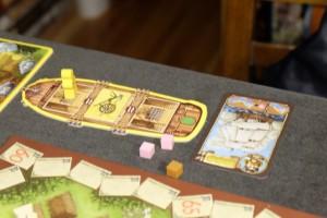 Première étape pour prendre la mer : recruter un capitaine, de valeur 1 à 3 pièces d'or, sachant que plus un capitaine a couté cher moins il coutera de cubes pour déplacer son bateau. Une bonne idée. Ensuite, il faut charger sa cale : Tristan y a mis un membre de sa famille et une charrue. Bon vent, matelot !