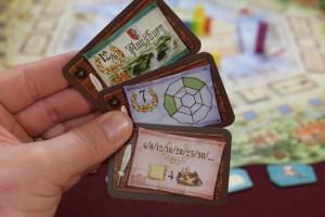 En main, chaque joueur possède 3 cartes d'objectifs qu'il va essayer de réaliser en fin de partie. Les trois miennes sont les suivantes : être majoritaire dans la région d'Augsburg (12PV) ou 2ème (6PV), avoir des personnages placés comme sur la carte (7PV par paire réalisée) et, enfin, avoir placé mes personnages sur des cases de valeur 4... Ca donne à penser...