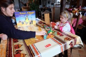 Julie fait progresser son pion bleu à l'aide du bateau en le positionnant contre son pion pour aller sur la case de son choix à l'extrémité du bateau. Leila semble trouver qu'une de ses cartes est intéressante... :-)