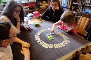 La partie a débuté. A tour de rôle, on retourne une carte du centre, en fonction de la couleur indiquée par le dé. Ensuite, dès qu'une carte de chaque partie est sortie, il deviendra possible de pointer du doigt, voire en l'écrasant ;-) la carte du tour qui correspond aux trois parties retournées. Oui, c'est un jeu de rapidité...