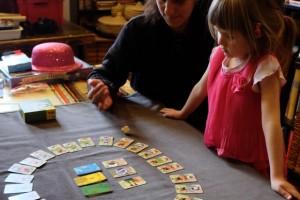 Julie lance le dé, la tension est à son comble : en effet, il n'y a aucun temps mort puisqu'à chaque tirage, une carte est susceptible d'être pointée ! Comment n'y a-t-on pas pensé avant ?